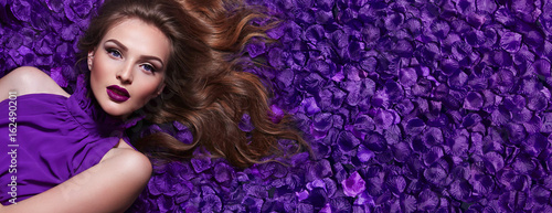 Foto op Aluminium Spa The girl in the petals. Beautiful young girl lies in the violet petals in a long dress. Glamor, luxe. Hair - curls. Makeup - arrows, purple lipstick. Love, romance.