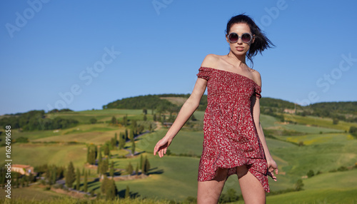 Fotografie, Obraz  View of a girl in red dress in Tuscany hills, Italy