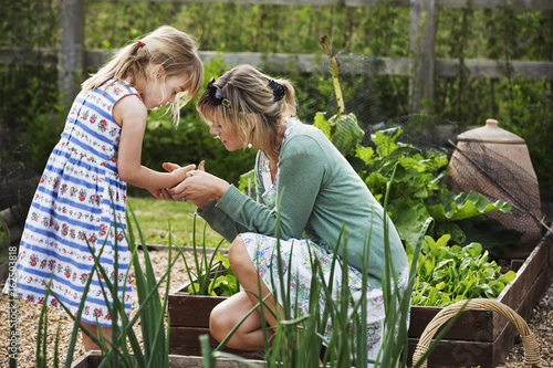 Woman kneeling in a garden by a raised vegetable bed, looking at the hand of a young girl beside her.