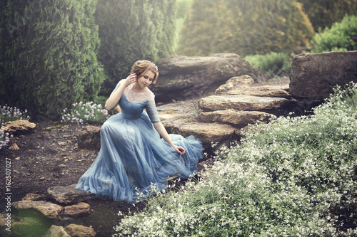 Fotografie, Tablou A beautiful young girl like Cinderella is walking in the garden.