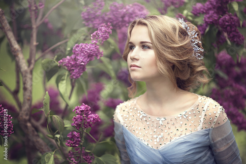 Fotomural Portrait of a beautiful young blond woman in lilac bushes, admiring flowers