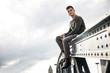 Young man sitting on railing of a bridge