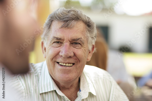 Smiling senior man socializing on a garden party