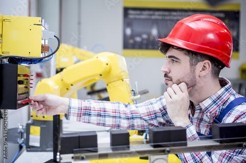 Man wearing hard hat adjusting industrial robot