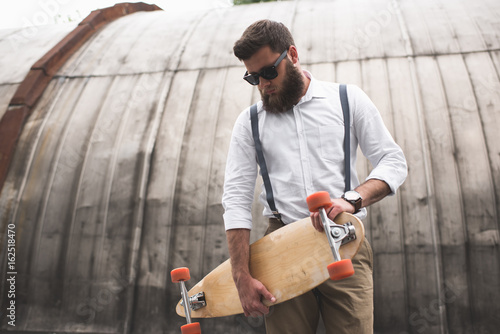 stylish bearded man in sunglasses and suspenders holding longboard