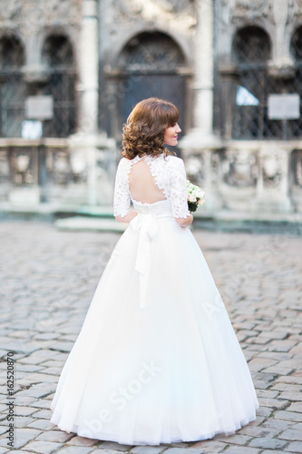 Fototapeta The back view of the bride with the wedding bouquet in the street