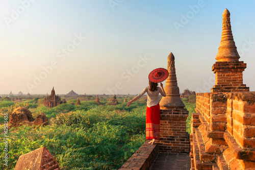 Fotografie, Obraz  A girl with a traditional Burmese umbrella relaxing in an ancient temple during sunset, Bagan,Myanmar