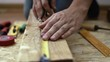 Close-up of constructor hands measuring lumber with tape on the floor.