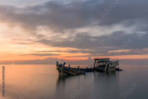 Foto auf AluDibond Schiff An old shipwreck or abandoned shipwreck taken during a beautiful sunset , Wrecked boat abandoned stand on beach or Shipwrecked off the coast of Thailand.