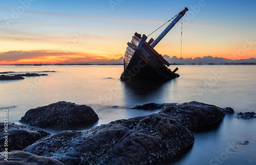 Foto op Canvas Schip An old shipwreck or abandoned shipwreck taken during a beautiful sunset , Wrecked boat abandoned stand on beach or Shipwrecked off the coast of Thailand.