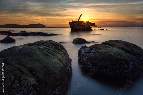 Keuken foto achterwand Schip An old shipwreck or abandoned shipwreck taken during a beautiful sunset , Wrecked boat abandoned stand on beach or Shipwrecked off the coast of Thailand.