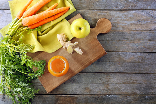 Jar of carrot juice with fresh ginger and apple on wooden background Canvas Print