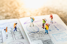 Travel Concept. Group Of Miniature With Backpack Walking And Standing On Passport With Immigration Stamps.