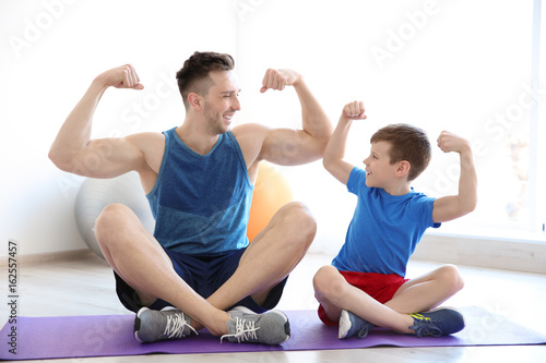 Fotografía  Dad and son sitting on floor and showing muscles indoors