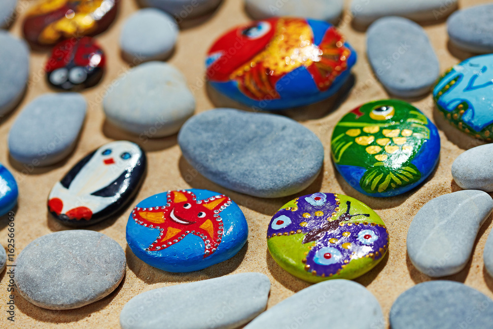 Fototapeta Rounded colorful stones pebbles shingle with pictures painted on them