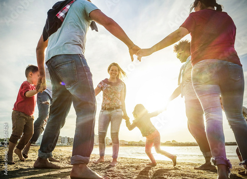 Valokuva  Diverse culture families playing with children on the beach - Sons and parents r