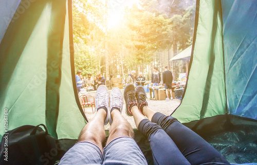 Spoed Fotobehang Kamperen Pov view of happy couple inside tent at camping wood festival - Young people having fun on summer vacation into the wood - Travel,love,nature concept