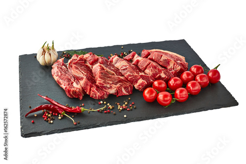 Fresh raw beef steaks with pepper and tomatoes on black slate board Poster