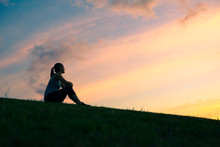 People Enjoying Nature. Woman Sitting On A Hill Watching The Sunrise.