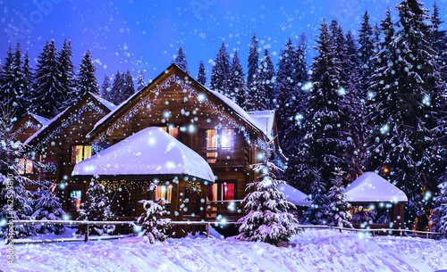 Fotografiet A fairy-tale house in the woods amid the snow-covered fir trees, Christmas landscape