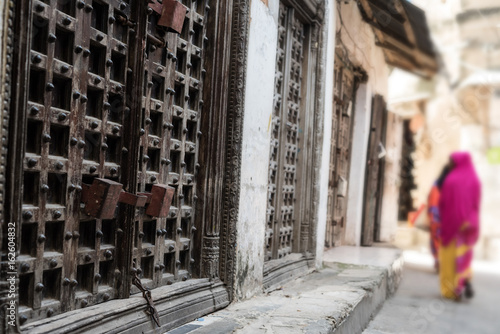 Poster Zanzibar typical Zanzibar town street with old iron doors and wooman walking away, Africa
