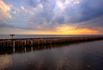 Evening sky,rows of bamboo sticks in the sea and cement bridge near Matchanu Shrine,Phanthai Norasing,Mueang Samut Sakhon District,Samut Sakhon,Thailand.