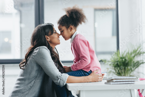 side view of african american mother able to kiss her little daughter Wallpaper Mural