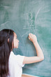 Girl writing a sum on a blackboard