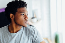 Melancholic Headshot Portrait Of Young Black Man Looking Aside Isolated On Blurred Indoors Background.