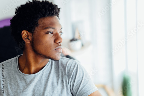 Photo Melancholic headshot portrait of young black man looking aside isolated on blurred indoors background