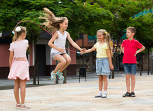 Children With Jumping Rope At Playground.