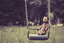 Old Toy Teddy Bear Sitting On Swing In Park