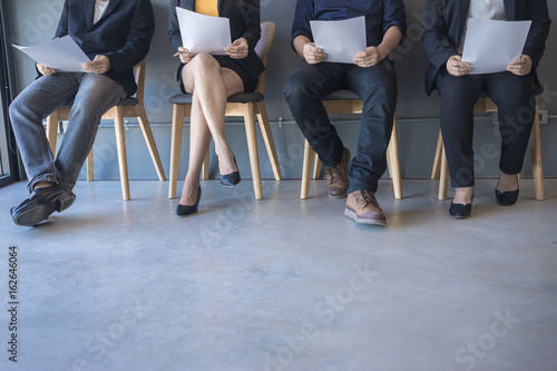 Obraz Group of peoples are sitting to review the documents while waiting for a job interview. - fototapety do salonu