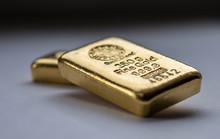 Two Cast Gold Bars On A Grey B...
