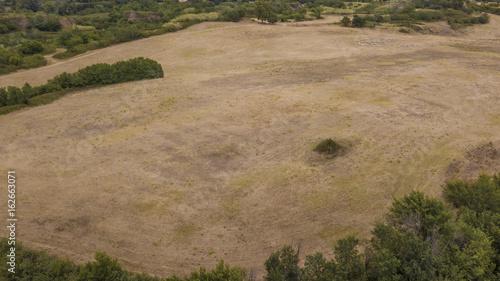 Vista su un paesaggio bucolico con un vasto campo incoltivato dove nasce spontan Fototapeta