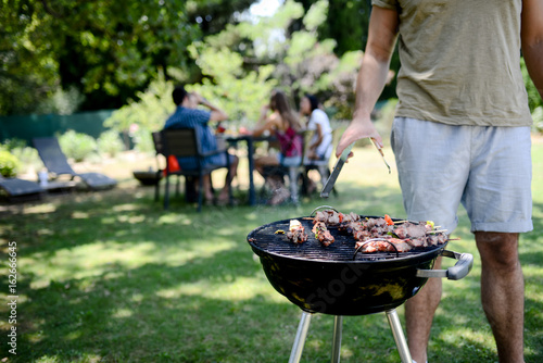 Photo sur Toile Grill, Barbecue close up of a barbecue grill with meat and sausages cooking during summer garden party with people in background