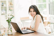 Portrait of happy beautiful young coonfident Asian woman smile while working with laptop indoor