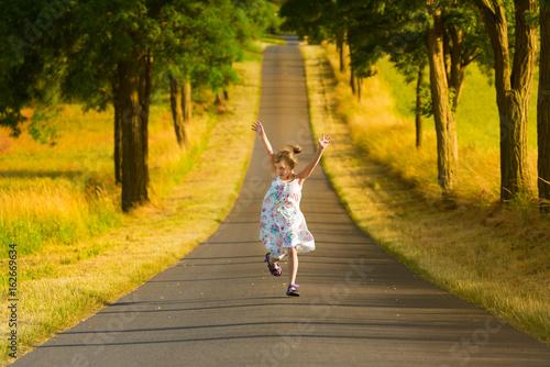 Fotografie, Obraz  Kleines Mädchen in Sommerkleid läuft springend und jubelnd eine Straße entlang u