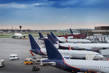 Many Airplanes Near The Terminal In An Airport At The Sunset
