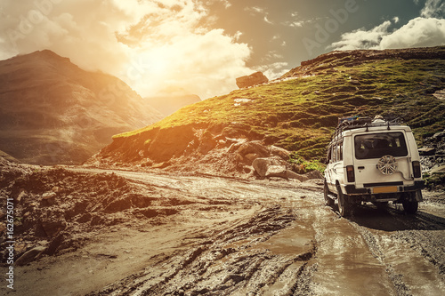 Fotomural  Off-road vehicle goes on the mountain way during the rainy season