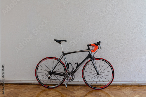 Tuinposter Fiets Race bike next to white wall