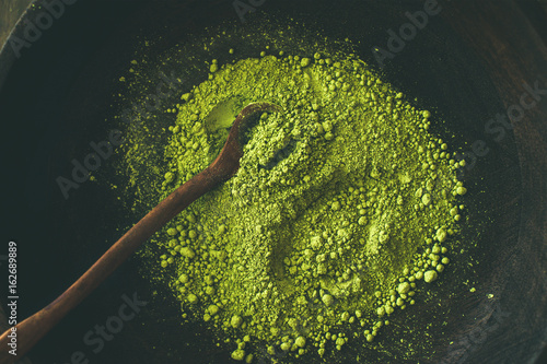 Japanese Matcha green tea powder in dark wooden bowl with spoon, top view. Clean eating, healthy, diet food concept
