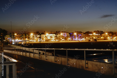 Fotografía  Night view of a Mediterranean beach with illuminated promenade