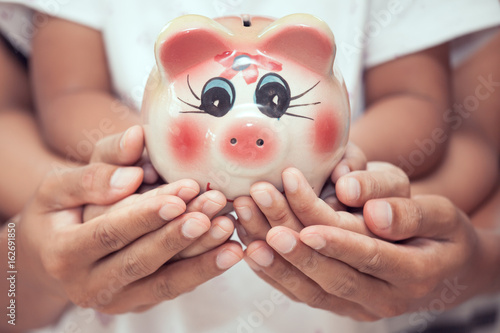 Fényképezés Piggy bank in child kid ,mother and father hands in vintage color tone