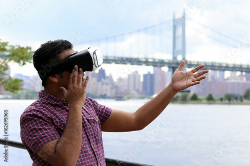 Fotografia, Obraz  Young handsome man wearing virtual reality goggles headset while standing infont