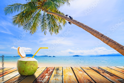 Coconut juice on wood table with coconut tree and sea background in summer, Summer holiday concept Wallpaper Mural