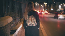 Brunette Woman With Backpack Walking Late At Night. Attractive Girl Goes Through The City Centre Near Road In Evening.