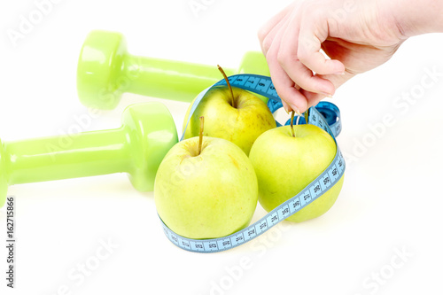 Fotografering  Trio of apples wrapped with cyan flexible ruler in hands