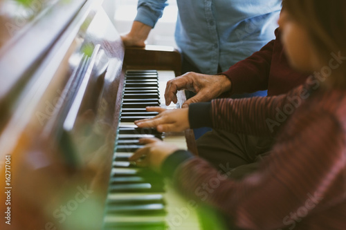 Midsection of woman standing by boy and great grandfather playing piano