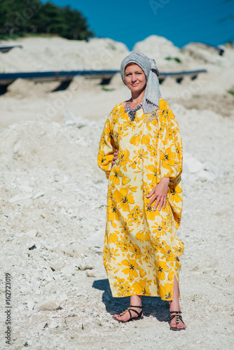 Beautiful woman in yellow dress in the Sands of very hot weather